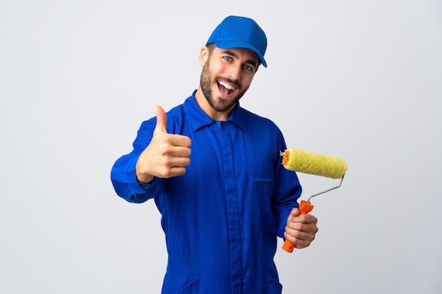 Maler mann hält einen farbroller auf weißer wand mit daumen hoch, weil etwas gutes passiert ist