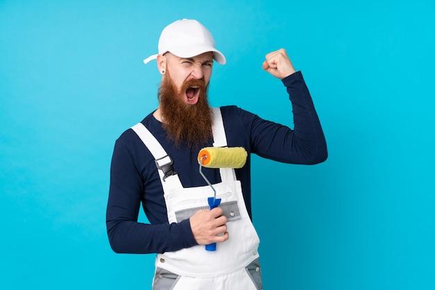 Maler mann mit langem bart über blauer wand macht starke geste