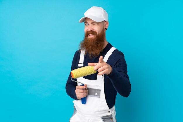 Maler mann mit langem bart über blauer wand zeigt finger auf sie