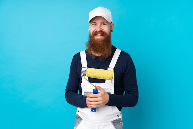 Maler mann mit langem bart über isolierten blauen wand applaudiert