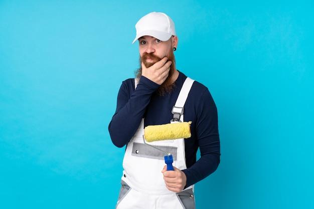 Maler mann mit langem bart über isolierten blauen wand lachen