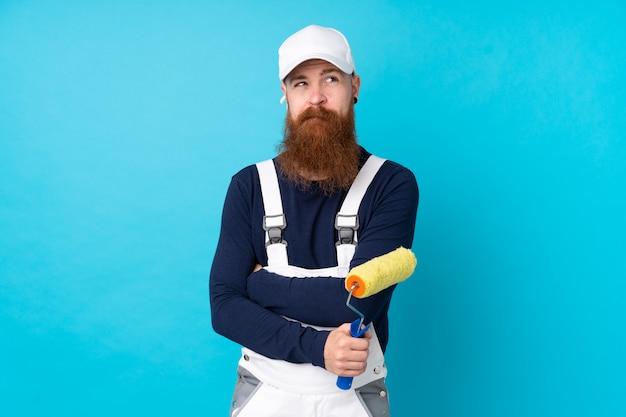 Maler mann mit langem bart über isolierter blauer wand, die eine idee denkt