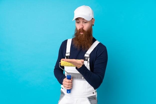 Maler-mann mit langem bart über isolierter blauer wand, die imaginären copyspace auf der handfläche hält