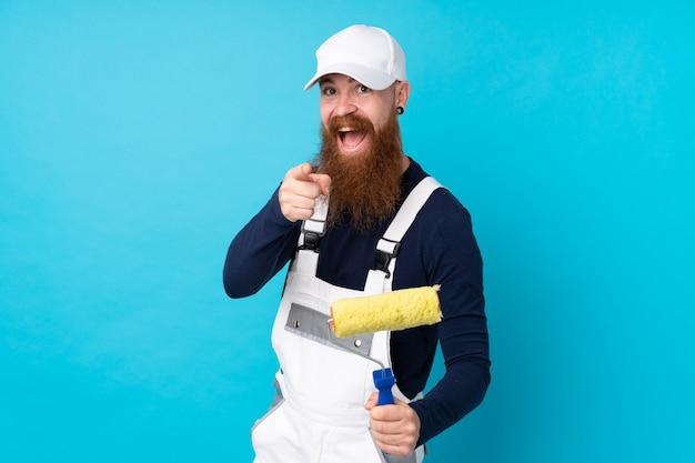 Maler mann mit langem bart über isolierter blauer wand zeigt finger auf sie