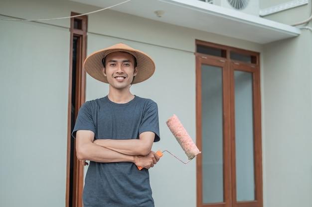 Maler tragen kappen mit gekreuzten händen, die farbroller im hochbau halten