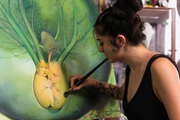 Maler vervollständigt ihre malerei in ihrem studio