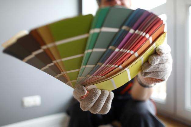 Maler zeigt farbmuster zur reparatur. der mensch wählt ein farbschema für die wände im haus