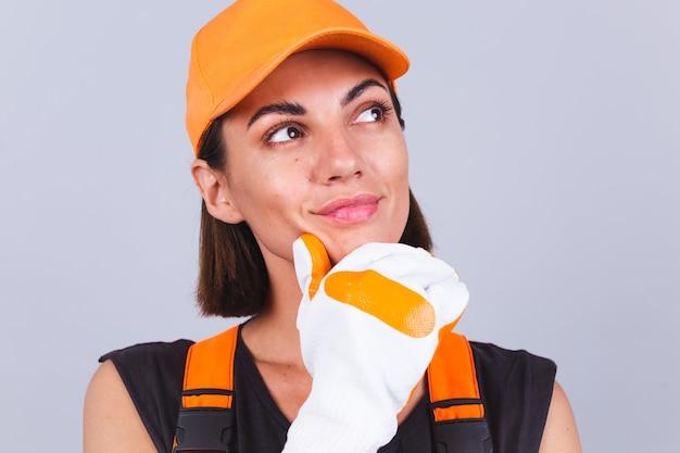 Malerarbeiterfrau in overalls und handschuhen auf grauer wand glückliches positives lächeln nachdenklicher blick beiseite