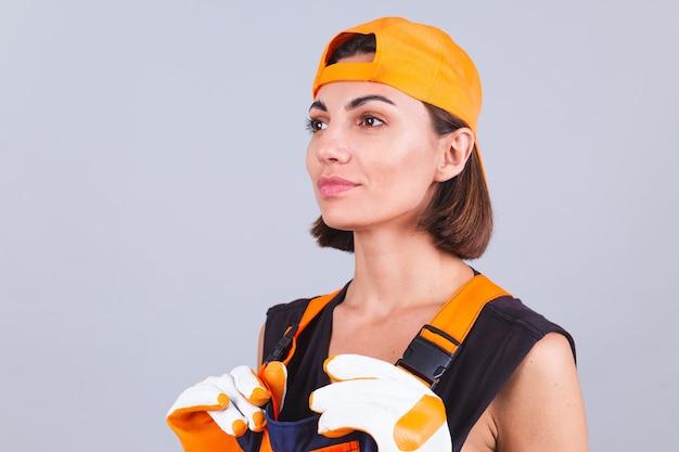 Malerarbeiterin in overalls und handschuhen an grauer wand mit ruhigem, selbstbewusstem lächeln beiseite