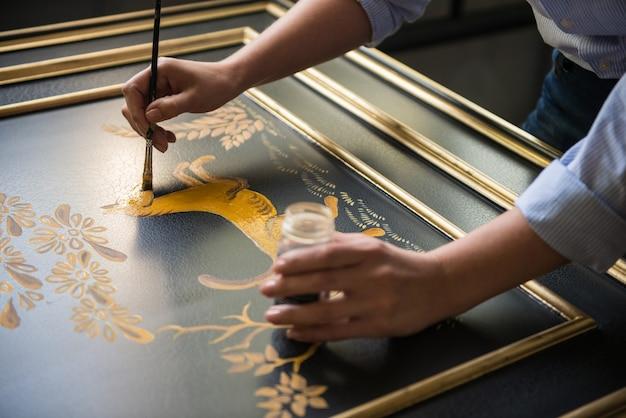 Malerdekorateur zeichnet muster von blumen und tieren