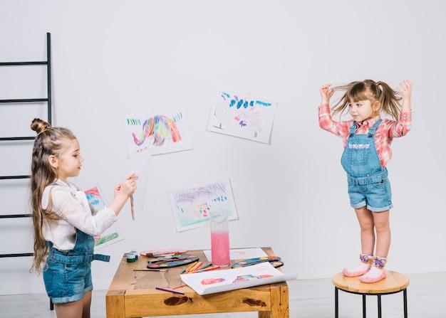 Malerei des kleinen mädchens, die mädchen auf stuhl aufwirft