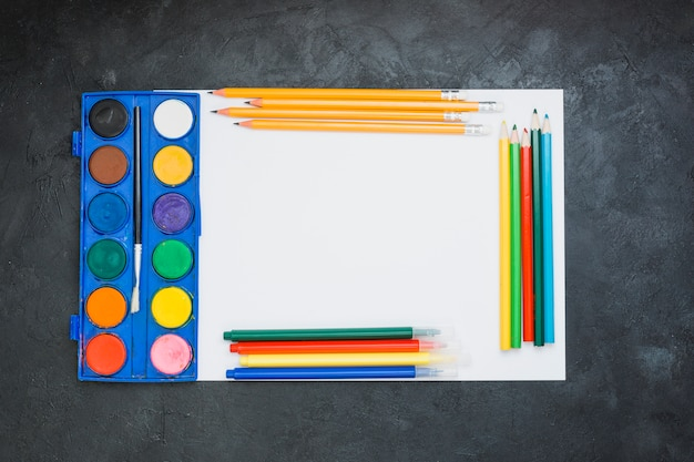 Malereiausrüstung auf weißbuchblatt über hintergrund des schwarzen schiefers