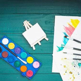 Malereiausrüstung und hand gezeichnetes blatt über gemaltem holztisch