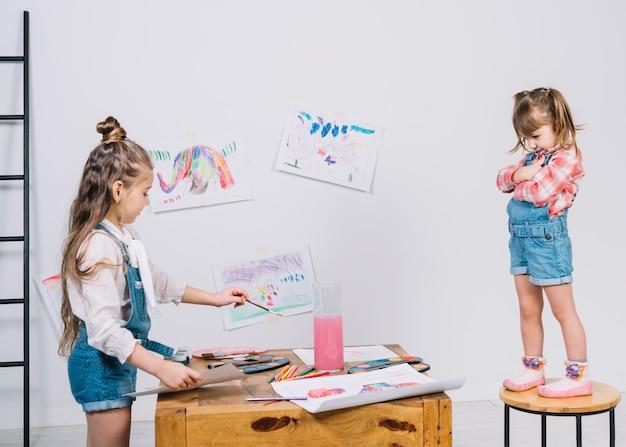 Malereimädchen des kleinen mädchens auf stuhl