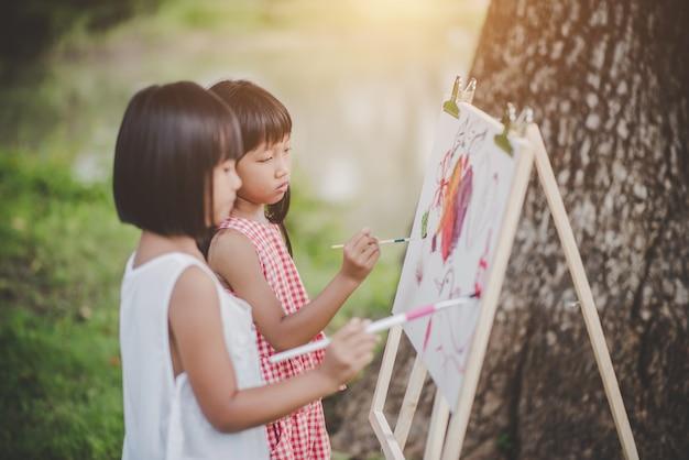 Malereimaler-kunstzeichnung mit zwei kleinen mädchen im park