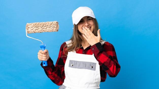 Malerfrau auf lokalem blauem glücklichem und lächelndem kegelmund mit hand