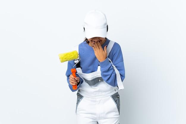 Malerfrau über isolierte weiße wand glücklich und lächelnd, die mund mit händen bedeckt