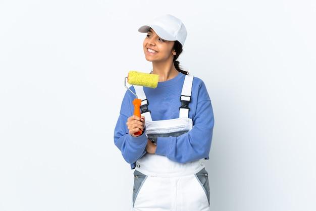 Malerfrau über isolierte weiße wand glücklich und lächelnd
