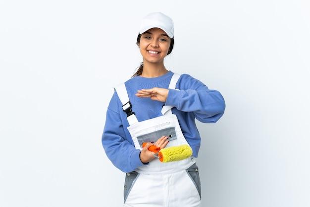 Malerfrau über isoliertem weißem hintergrund, der imaginären copyspace auf der handfläche hält, um eine anzeige einzufügen
