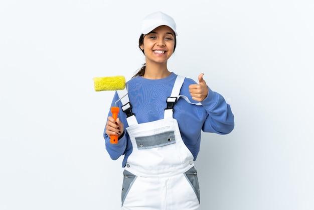 Malerfrau über isoliertem weißem hintergrund, der imaginären copyspace auf der handfläche hält, um eine anzeige und mit den daumen nach oben einzufügen