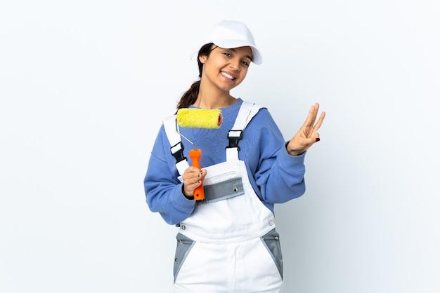 Malerfrau über isoliertem weißem hintergrund glücklich und drei mit den fingern zählend