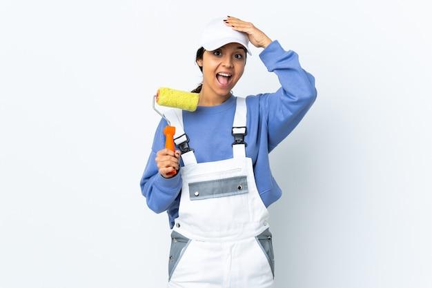 Malerfrau über isoliertem weißem hintergrund überrascht und finger zur seite zeigend