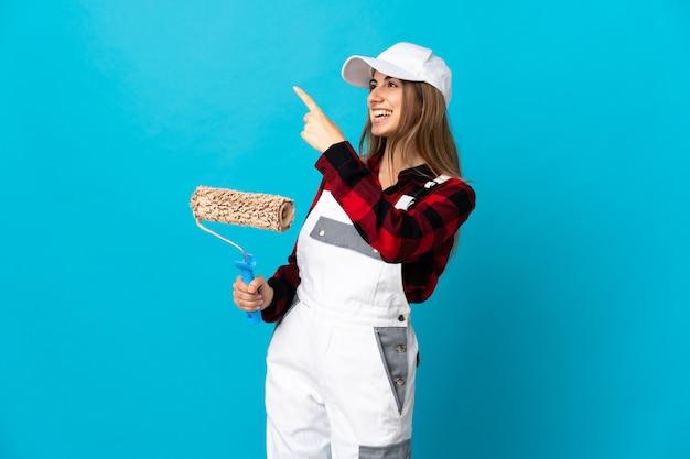 Malerfrau über isolierter blauer wand, die mit dem zeigefinger eine große idee zeigt