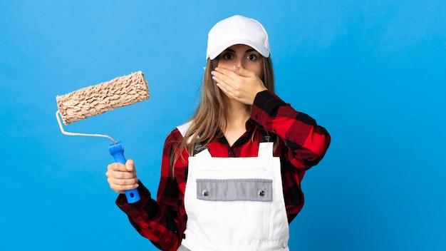 Malerfrau über isolierter blauer wand, die mund mit hand bedeckt