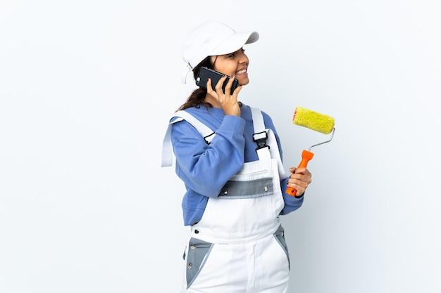Malerfrau über isolierter weißer wand, die ein gespräch mit dem mobiltelefon mit jemandem hält