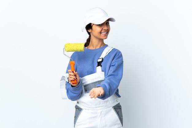 Malerfrau über isolierter weißer wand, die imaginären copyspace auf der handfläche hält, um eine anzeige einzufügen