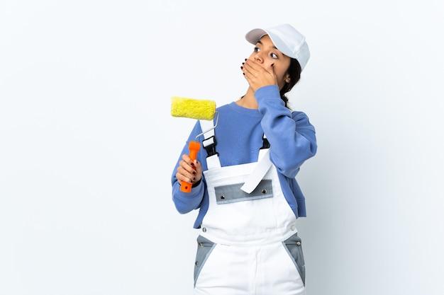 Malerfrau über isolierter weißer wand, die überraschungsgeste tut, während sie zur seite schaut