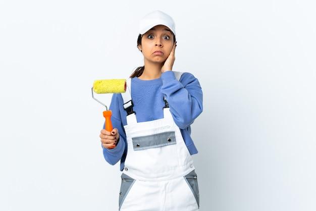 Malerfrau über isolierter weißer wand frustriert und ohren bedeckend