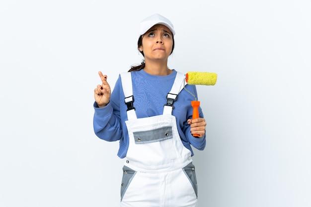 Malerfrau über isolierter weißer wand mit den fingern, die kreuzen und das beste wünschen