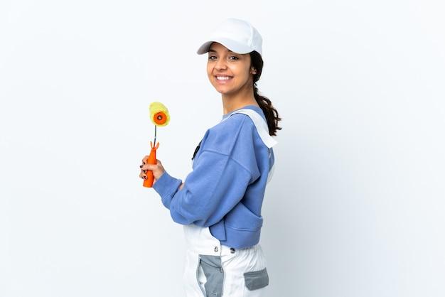 Malerfrau über isolierter weißer wand mit verschränkten armen und nach vorne schauend