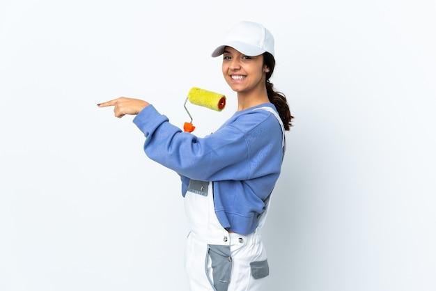 Malerfrau über lokalisiertem weißem hintergrund, der finger zur seite zeigt und ein produkt präsentiert