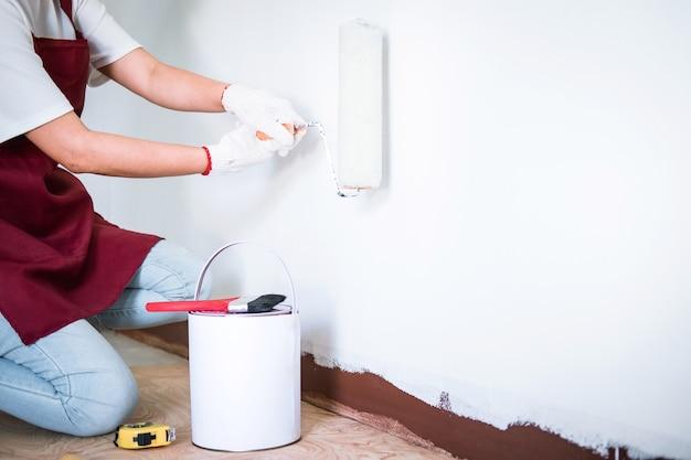 Malerhand in der weißen handschuhmalereiwand mit farbenrolle im raum, in der form und in der struktur