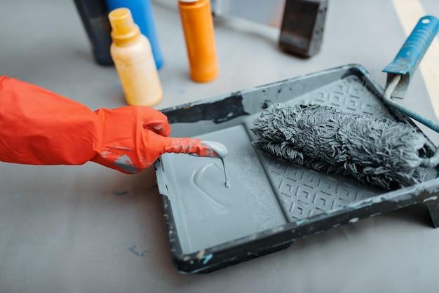 Malerhandschuh imprägniert die walze mit farbe.