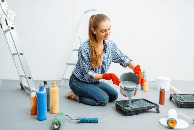 Malerin bereitet sich auf die arbeit vor. hausreparatur, lachende frau bei der renovierung der wohnung, renovierung der zimmerdekoration