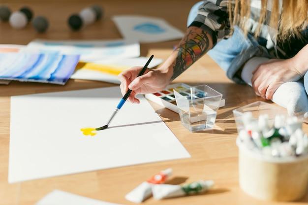 Malerin, die auf dem boden sitzt