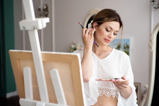 Malerin, die im kunststudio unter verwendung der staffelei zeichnet. porträt einer jungen frau, die mit ölfarben auf weißer leinwand malt, seitenansichtporträt