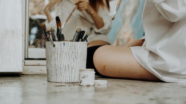 Malerin, die vor spiegel auf dem boden sitzt und zeichnet. interieur des kunstateliers. zeichenzubehör, ölfarben, künstlerpinsel