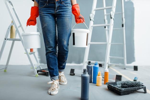 Malerin hält eimer mit farben. hausreparatur, glückliche frau, die wohnungsrenovierung macht, zimmerdekoration renovieren
