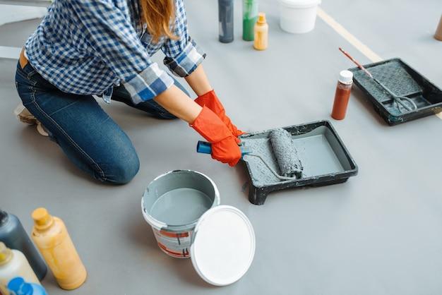 Malerin imprägniert die walze mit farbe. hausreparatur, lachende frau bei der renovierung der wohnung, renovierung der zimmerdekoration