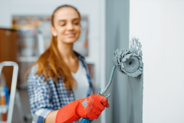 Malerin in handschuhen malt die wand. hausreparatur, lachende frau, die wohnungsrenovierung macht, zimmerrenovierung