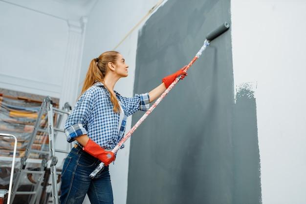 Malerin in handschuhen malt die wand.