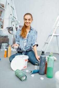 Malerin mischt farben im eimer. hausreparatur, lachende frau bei der renovierung der wohnung, renovierung der zimmerdekoration