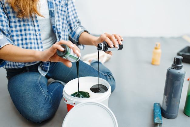 Malerin mischt farben vor dem malen. hausreparatur, glückliche frau, die wohnungsrenovierung macht, zimmerdekoration renovieren