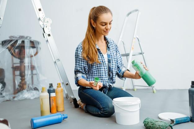 Malerin mischt farben vor dem malen. hausreparatur, glückliche frau, die wohnungsrenovierung macht
