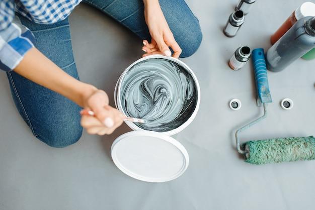 Malerin mischt schwarze und grüne farben im eimer, nahaufnahme. hausreparatur, lachende frau bei der renovierung der wohnung, renovierung der zimmerdekoration