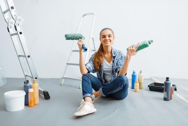 Malerin mit farbe und rolle auf dem boden sitzend. hausreparatur, glückliche frau, die wohnungsrenovierung macht